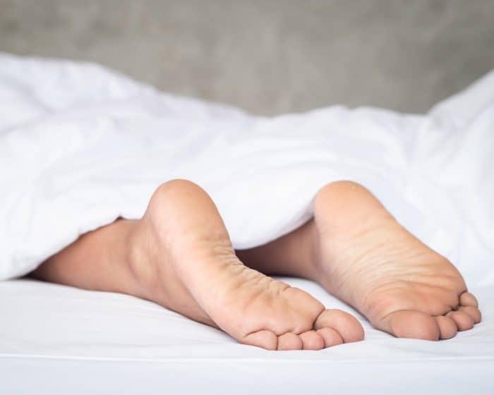 Nohy vykukující zpod peřiny